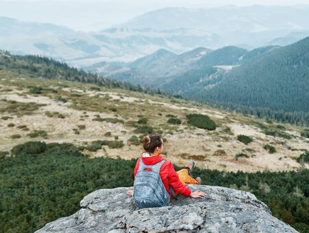 woman hiker in red jacket sitting on the cliff in mountains and meditating