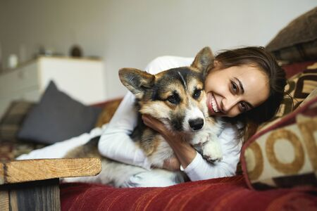 Portrait of happy smiling woman with her cute Welsh Corgi dog lying on couch at home. Beautiful brunette female hugging funny puppy, enjoing morning weekend, has good relationships with pet. Imagens