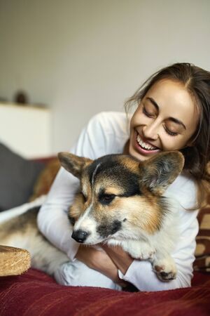Portrait of happy smiling woman with her cute Welsh Corgi dog lying on couch at home. Beautiful brunette female hugging funny puppy, enjoing morning weekend together, has good relationships with pet. Focus on the dog. Imagens