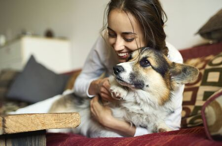 Portrait of happy smiling woman with her cute Welsh Corgi dog lying on couch at home. Beautiful brunette female embracing funny puppy, laughing, enjoying time together, has good relationships with pet.