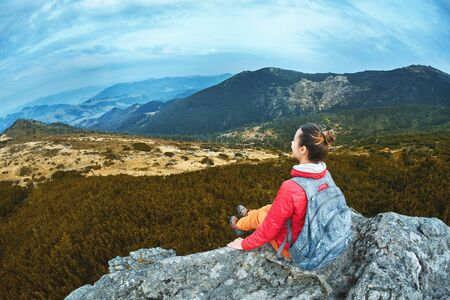 woman hiker in red jacket sitting on the cliff on high view point in Carpathians mountains, resting,enjoying and sightseeing
