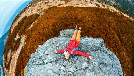 top view of woman hiker in red jacket lying on the cliff in mountains with raised hands