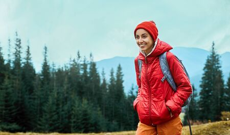 woman hiker with small backpack wearing in red jacket and orange pants walks by trail through pine woods in the Carpathians mountains, Western Ukraine.