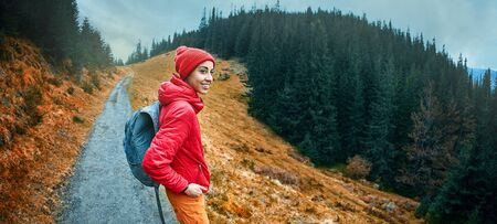woman hiker with backpack, wearing in red jacket and orange pants, standing on mountain trail while hiking on cloudy sky and woods background and sightseeing, Western Ukraine.