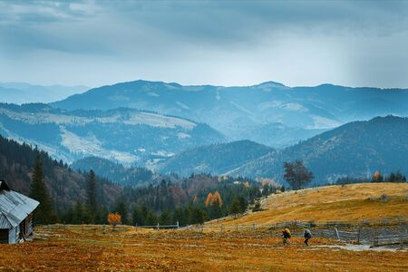 beautiful view of an autumn mountain landscape with a cloudy sky, Western Ukraine. two hikers walking trail on mountain slope to the old wooden hut Imagens