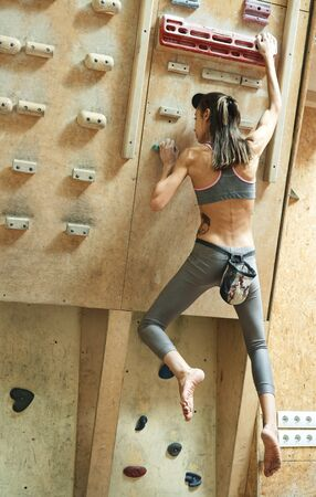 Slim athletic woman climber on campus board getting ready to climbing and doing exercise for fingers strength. Sporty girl exercising and training in climbing gym. Concept of sport, overcoming, healthy lifestyle.