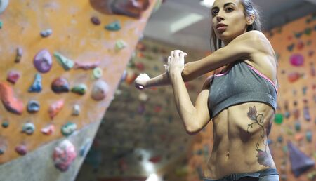 Athletic woman with muscular naked torso doing stretching before climb in indoor climbing gym. Exercising and training in climbing gym. Concept of strength, sport, healthy lifestyle.