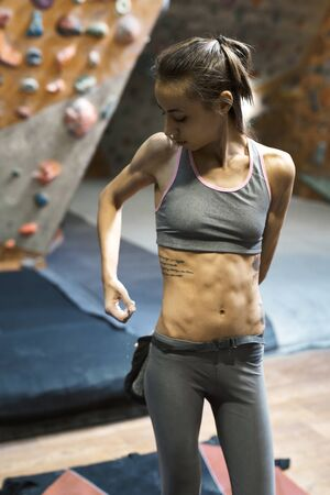 Woman climber is chalking hands with white chalk powder before climb in indoor climbing gym. Athletic muscular woman with muscular naked torso getting ready to climbing. Exercising and training in climbing gym. Concept of strength, sport and healthy lifestyle.