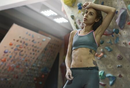 Athletic woman with muscular naked torso is training in climbing gym indoor. Girl is tired and resting. Exercising and training in climbing gym. Concept of strength, sport, healthy lifestyle. Imagens