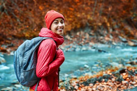 pretty woman hiker in bright red outdoor clothes is standing outdoors on the mountain river and forest background and cheerfully looking at camera. Traveling, hiking and actyve lifestyle concept Imagens