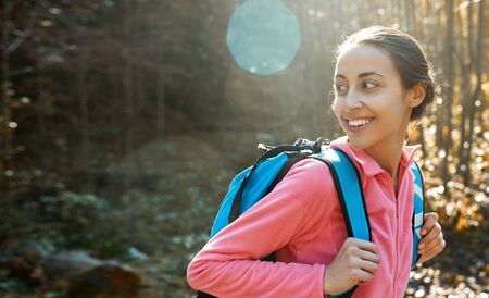 portrait of woman hiker with small backpack, wearing in pink fleece jacket, standing on pine woods background in the Carpathians woody mountains, Western Ukraine. happy smiling woman looking back at side from camera Imagens