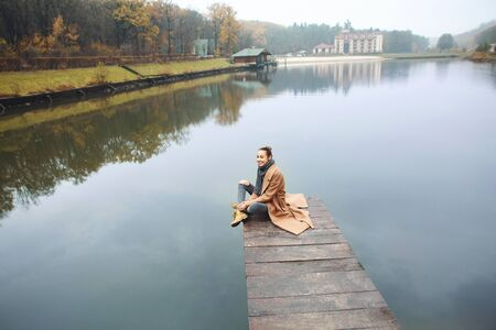 Happy woman sitting on the wooden pier in the park at autumn. Beautiful young stylish female wearing long beige coat enjoying view over the lake at cloudy autumn day. Imagens