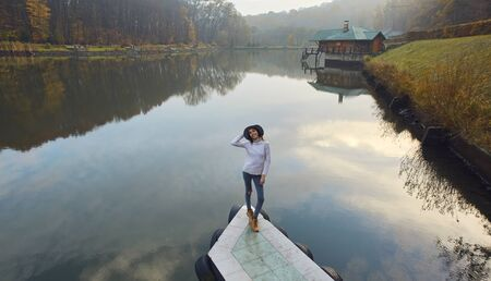 Stylish young woman in a warm sweater and hat, standing on pier by the lake in the park at autumn. Female smiling, enjoying view over the lake at cloudy autumn day. Back view. Imagens