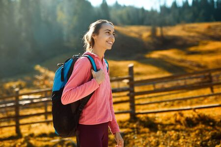 woman hiker with backpack walking outdoors. woman standing on the yellow meadow and green woods background in mountain village Dzembronya, Western Ukraine.