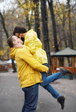 couple in yellow jackets embracing and kissing, walking in the autumn park. Happy young family spends time together. Love and good relationship concept. Autumn concept.