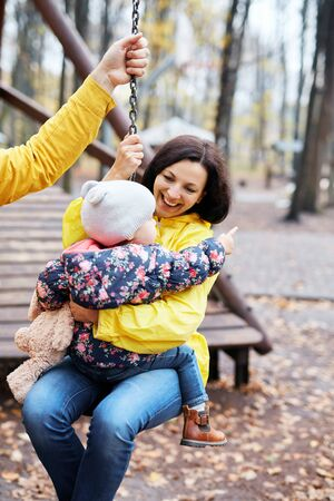 Happy mother with daughter walking in the autumn park. Loving young mother embracing cute kid daughter, enjoying time together outdoors at weekend. Woman wearing yellow waterproof raincoat. Family, motherhood and Happy Mothers Day concept.