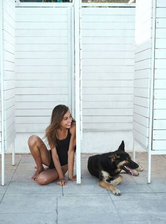 Young attractive tanned woman in a black swimsuit sitting down, posing on a white background. Beautiful slim girl having fun, enjoying good sunny day at vocation. A big black dog is lying nearby. Lifestyle, happiness, vacation concept.