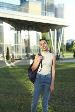 Portrait of smiling female student with a backpack going to college, happy about the new educational year. Education, knowledge concept, copy space.