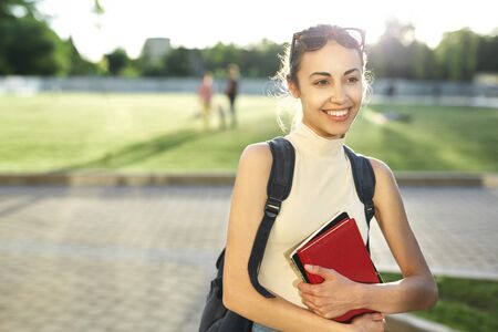 Portrait of smiling female student with a backpackand books in campus, happy about the new educational year. Education, knowledge concept, copy space.