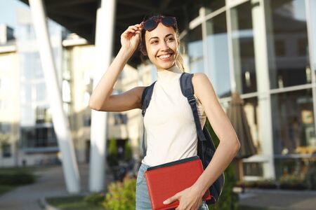 Beautiful happy woman in sunglasses with a backpack going to college. Young female university student with books in campus. Education, knowledge concept, copy space.