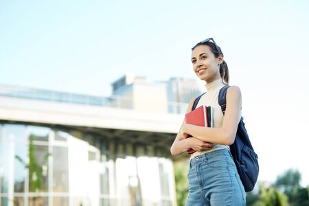 Beautiful happy woman with a backpack going to college. Young female university student with books in campus. Education, knowledge concept, copy space.