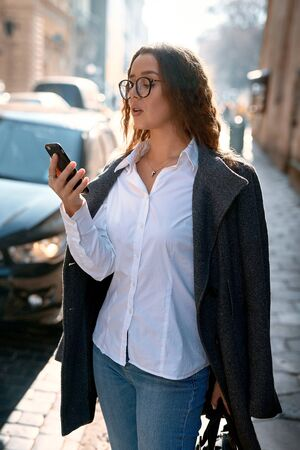 Portrait of a business woman in eyeglasses, white shirt and gray jacket using smartphone on the street. City business woman going to to work place office. Business lifestyle