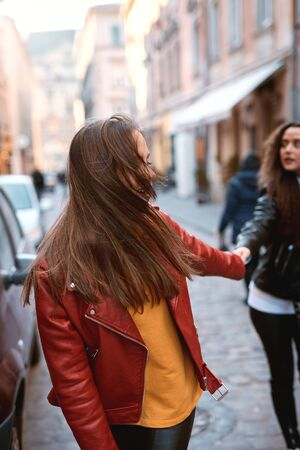 portrait of young female friends in colored leather biker jackets and hoodies holding hands while walking down the street. Stylish girls having fun, expressing positive emotions to camera.