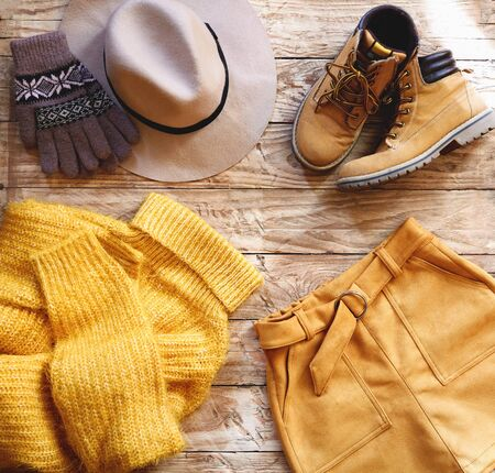 Female knitted yellow sweater, orange skirt, hat, gloves and boots on wooden background top view. Autumn trendy lady clothes set. Fall fashion look. Creative autumnal Flat lay. Imagens