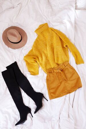 Female knitted yellow sweater, orange skirt, hat and thigh high heeled boots on a white sheet background top view. Autumn trendy lady clothes set. Fall fashion look. Creative autumnal Flat lay.