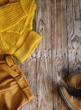 Female knitted yellow sweater, orange skirt and boots on wooden background top view. Autumn trendy lady clothes set. Fall fashion look. Creative autumnal Flat lay.