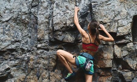 young slim muscular woman rockclimber climbing on tough sport route, searching, reaching and gripping hold. climber makes a hard move. outdoors rock climbing and active lifestyle concept