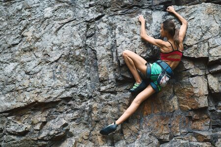 Sports Woman With slim fit body Climbing The Rock Having Workout In Mountains. rock climbing hard moves, searching holds, overhand