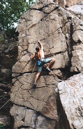 Back view of unrecognizable man rockclimber climbing on tough sport route, reaching and gripping hold. climber makes a hard move. outdoors rock climbing and active lifestyle concept.