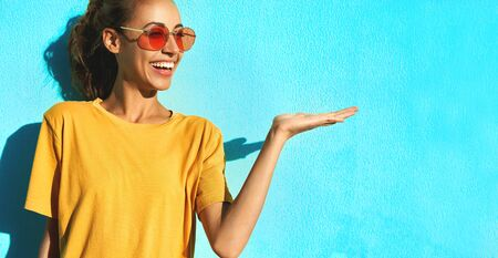 portrait of fashionable smilingl young woman in trendy red eyeglasses posing posing emotionally and smiling on blue background, wearing yellow t-short. Happy girl has attractive look, posing to the camera and showing different emotions.
