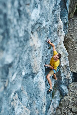 top view of man rock climber in yellow t-shirt, climbing on a cliff, searching, reaching and gripping hold, attaching rope. outdoors rock climbing and active lifestyle concept, 4K stock footage