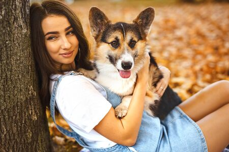 beautiful young brunette woman together with Welsh Corgi Pembroke dog in a autumn park outdoors. Young female owner huging pet in park at fall on the orange foliage background. Concept friendship with dog and human Banco de Imagens