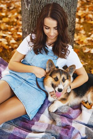 happy woman sits together with Welsh Corgi Pembroke dog in a park outdoors. Young female owner huging pet in park at fall on the orange foliage background. Concept friendship with dog and human Banco de Imagens