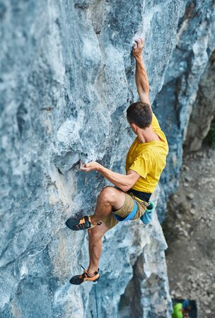 young strong man rock climber climbing on a high vertical limestone cliff, reaching holds, making hard wide move and gripping hold, attaching rope. Conquering, overcoming and active lifestyle concept.