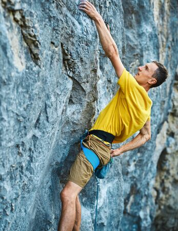 Young strong man climbing challenging route on a high vertical limestone cliff, resting and chalking hands. Conquering, overcoming and active lifestyle concept.