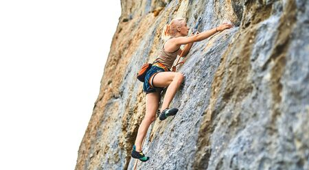 young woman rock climber Climbing The Rock Having Workout In Mountains, searching, reaching and gripping hold on white background. outdoors rock climbing and active lifestyle concept.