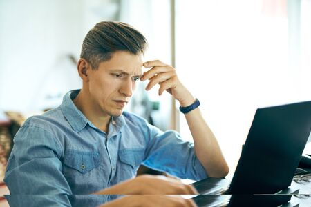 handsome man working using laptop computer at office. man texting, looking at laptop screen and showing reverie and concentration. Concept of resolving problems, management, investing in startups