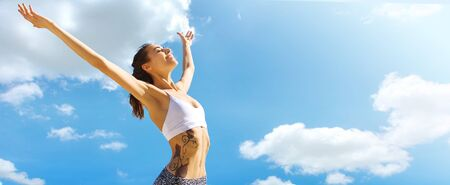 Happy woman with tanned slim body and tattoo posing in sport wear with raising hands against blue sky. Healthy smiling female enjoying sunny summer day. Summertime concept.
