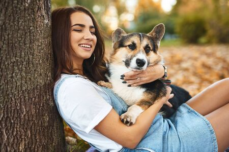 beautiful young brunette woman together with cute Welsh Corgi Pembroke dog in a autumn park outdoors. Young female owner huging pet in park at fall on the orange foliage background and laughing. Concept friendship with dog and human