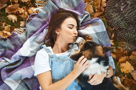happy beautiful girl lying together with Welsh Corgi Pembroke dog in a park outdoors. Young female owner huging and kissing pet in park at fall on the orange foliage background. Concept friendship with dog and human