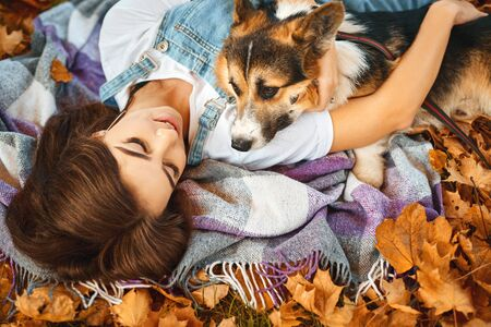 smiling happy woman together with Welsh Corgi Pembroke dog in a park outdoors. Young female owner huging pet in park at fall on the orange foliage background. Focus on the woman. Concept friendship with dog and human Banco de Imagens