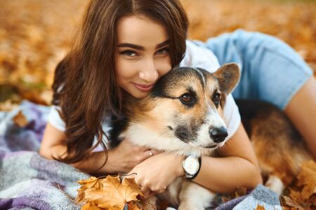 happy beautiful girl lying together with Welsh Corgi Pembroke dog in a park outdoors. Young female owner huging pet in park at fall on the orange foliage background. Concept friendship with dog and human