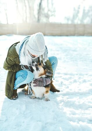 Young happy woman in woolen hat and long warm scarf huging and stroking her pet in snowy winter park at frosty sunny day. Happy time together, cute dog Welsh Corgi Pembroke, winter holodays.