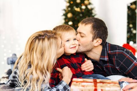 Young parents kissing their son and giving a Christmas present to little boy at Chrismas morning in bed. Christmas family spending time together at home, Xmas tree on background. Merry Christmas and Happy New Year.