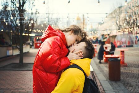young romantic couple in love hugging, kissing, wearning in bright yellow and red down jackets. Handsome man carrying young attractive woman while walking on the street. spending time together, having a date. urban background. Romantic, love and Valentines Day. Reklamní fotografie - 138200737