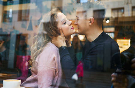 young romantic couple sitting over the window in cafe, embracing and kissing. Cute boyfriend and girlfriend having a date, enjoying together Valentines day holiday. View through cafe window. Foto de archivo